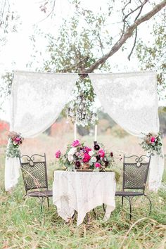 Vintage pink and plum sweetheart table in the woods on this moody day. This gorgeous vintage setting with a chandelier and lace is the perfect backdrop for every bride and groom head table. These vintage rentals are perfection with these amazing florals. 100 Layer Cake featured Vintage Indulgence March 2016