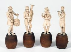 """A SET OF FOUR GERMAN IVORY FIGURES, late 19th century, carved as musicians playing a flute, French horn, tuba and drum, each standing on a wooden barrel, unsigned, 6 3/4"""" - 7"""" high """