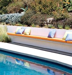 Built-in benches offer easy seating for this backyard pool. tied into a retaining wall perhaps