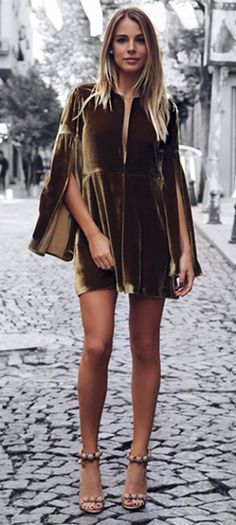 A velvet dress + classic Christmas style + utterly chic + bare legs and heels + winter cold + tights + classic trench coat + festive and stylish look + Aysegul & Yasemin.   Brands not specified.