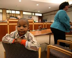 After his adoption was finalized, 3-year-old  Dante Drankiewicz looks back at the gallery in Circuit Judge Karen E. Christenson's courtroom on Adoption Day. In Milwaukee County, 17 families adopted 28 children.
