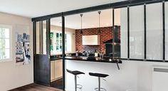 Vous rêvez d'une cuisine ouverte ? Découvrez cette rénovation à l'esprit industriel. Une cloison semi-ouverte façon verrière apporte lumière et modernité à la pièce.