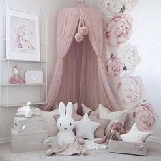 This space is so dreamy and romantic. A beautiful baby girls nursery. The flowers on the wall with the canopy are stunning! The pillows and the shelf with decor are gorgeous.