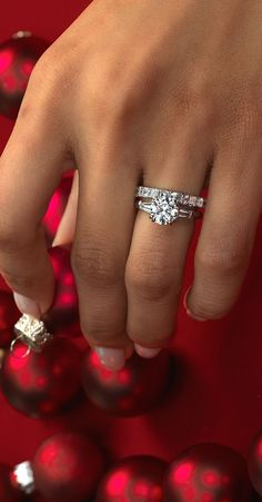 A pair of tapered baguette-cut side diamonds, set in platinum, flank the round center stone of your choice in this classic engagement ring.