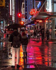 Vancity Rain  Neon lights splash colour on the rain soaked streets of downtown Vancouver. Looking up Granville Street at the corner of Robson Street. More spring rain is on the way. Captured in Vancouver British Columbia Canada  TBT March 23 2016