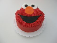 "Elmo Smash Cake 6"" Grass (Furry)-tipped buttercream Elmo face with fondant accents."
