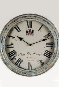 """Bring the feel of quaint, countryside home with the French Wall Clock. This timepiece has an antique appearance, and features luxurious typography. This piece is 14"""" round with a metal edge and featur"""