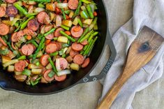 sausage and asparagus in cast iron skillet with wooden spoon