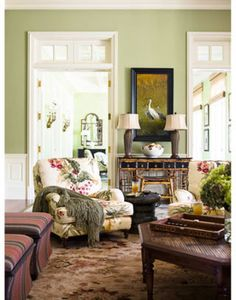"""Family room walls in Benjamin Moore's Lewiville Green are the color of """"a very ripe avocado."""" Club chairs from Lee Industries are covered in Summer Hill's Rio. Bamboo desk and stool from Randall Tysinger Antiques. Painting from T. Botero Galleries."""