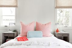 Chic girl's room with bed with no headboard dressed in soft white bedding, pink shams and blue bolster pillow flanked by white task lamps on gray nightstands.