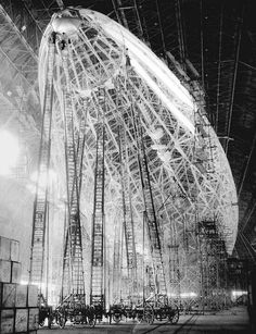 Surreal picture of a Zeppelin under construction, ca. 1935. Has anyone seen bigger ladders?