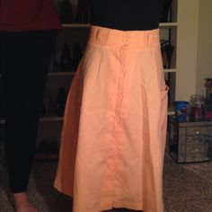Peach a-line vintage skirt Super cute spring skirt. Very pretty peach color. Buttons up the front and has pockets and belt loops! Has an a-line shape and really pretty movement when worn. Has no tags. Probably cotton or cotton blend. Sturdy material. Mannequin is a size 2 and I have the skirt clipped to stay on. Probably about a 4/6 and has stretchy waistband. Skirts
