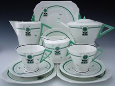 Green Martian afternoon tea set. This set comprises of a 1.5pint tea pot, hot water jug, sugar bowl, milk jug, sandwich plate, two cake plates, two saucers and two tea cups. This is a original set meaning all pieces were originaly purchased together in the very early 1930's and have been together ever since. All pieces bear the green Shelley backstamp appart from the tea pot and hot water jug which bear the rare black Shelley cartouche.