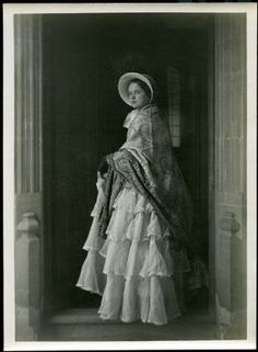 Photograph of a young woman in a bonnet, paisley shawl, black mitts, and gauzy tiered dress. Mid-1800s (date unknown). Fox Talbot Museum, Wiltshire.