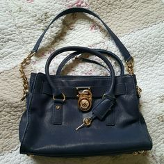 Authentic Michael Kors Bag- navy blue Gently used beautiful bag. The bag is overall in very good condition. There is a couple of small stains in the inside of the pocket at the very bottom corner which isn't noticeable until you flip the pocket inside out. The outside gold hardware is in good condition, just some very slight signs of wear. Bottom of purse has a very small scuff mark. No tears.  Height: ~9 inches Width: ~13 inches Michael Kors Bags Shoulder Bags