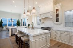 An open floor plan kitchen features creamy cabinets, marble countertops and an ornate range hood. Two kinds of marble tile is used as the backsplash: thin rectangles above the countertops and a herringbone pattern above the stove top.