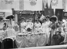 The sweets stall at the Women's Exhibition held at Prince's Skating Rink in May 1909. The exhibition was organised by the Women's Social and Political Union as a fundraising event. Over fifty stalls displayed items for sale that had been donated or made by suffragettes. Murals designed by Sylvia Pankhurst are visible in the background.