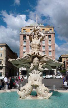 Rome - La fontaine du Triton. Dressée au milieu de la place Barberini, la fontaine du Triton fut créée en 1642 pour le pape Urbain VIII Barberini. Des dauphins soutiennent une énorme coquille sur laquelle est agenouillé Triton. La tiare pontificale, les clefs de saint Pierre et les armoiries des Barberini sont entralacées dans les nageoires des dauphins.