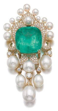 EMERALD, CULTURED PEARL AND DIAMOND /BROOCH, AMR SHAKER Set with a cushion-shaped emerald weighing 104.97 carats, to a decorative mount highlighted with brilliant-cut diamonds and cultured pearls, suspending a similarly set fringe, signed Shaker, together with a gold chain measuring approximately 920mm. by wteresa