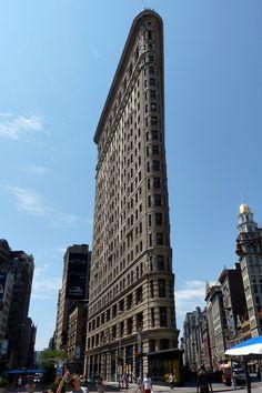 New York : Flatiron building Sa forme caractéristique est due au croisement à cet endroit de la 5ème Avenue avec Broadway, qui est la seule avenue de New York ne respectant pas les angles droits des autres artères. Il a donc fallu construire un immeuble en pointe à cette intersection.