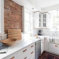 Well appointed white kitchen boasts an exposed brick wall flanked by window lit by glass pendants hung above a honed white marble countertop fixed against Kitchen Marble Top, Kitchen Splashback Tiles, White Shaker Kitchen Cabinets, Black Backsplash, Kitchen Cabinets Decor, Kitchen Drawers, Kitchen Ideas, Beadboard Backsplash, Backsplash Ideas