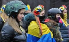 TOPSHOTS Activists of Maidan self-defence wearing helmets and crowns of flowers watch Kiev's communal services remove an opposition barricade on Grushevsky street in order to allow limited car traffic in accordance with an arrangement between anti-government opposition and the Ukrainian powers, in Kiev, on February 16, 2014. AFP PHOTO/ GENYA SAVILOV