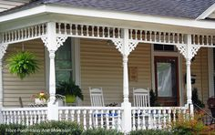 Front porch with turned columns, double rockers, table and chairs