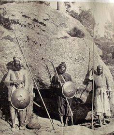Indian hill men, with shields, spears, tulwar sword and torador gun, wearng mail armor and helmets.