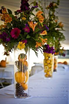 Fruit and pumpkins in vases for flower arrangements