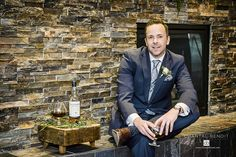 Cool groom in front of fireplace relaxing with his drink at Ale Amberwood Eatery & Lounge