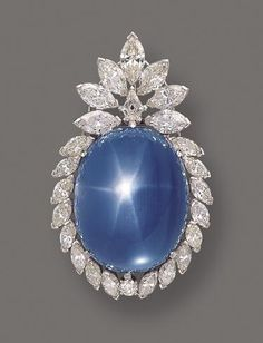 """""""Star sapphire and diamond pendant-brooch, circa 1955. The large oval-shaped star sapphire cabochon weighing approximately 145.00 carats, within a frame set with 23 marquise-shaped, 1 round and 1 kite-shaped diamond weighing a total of approximately 23.00 carats, mounted in platinum, with pendant hook."""""""