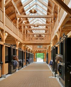 "The Beechwood Stables complex consists of three buildings; a riding arena, a horse barn and a service barn. The arena is fronted by a tall porch with a monumental fireplace framed by granite and Douglas fir columns and a ridgeline skylight. The porch leads to an observation room overlooking the arena. Horizontally bi-folding ""hangar"" doors along the arena's perimeter provide extraordinary light, views and ventilation. An enclosed link between the arena and stall barn accommodates space for a…"