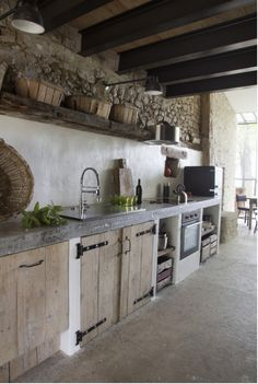 Rustic Kitchen with round stainless steel extractor and stone walls