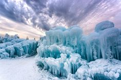 ice castles literally built by hand, a collision of caves, frozen waterfalls and glaciers, arch-ways, caverns and tunnels for people to explore. more than 5,000 icicles are grown each day, harvested/sculpted by creator brent christiansen and a team of arctic artists.