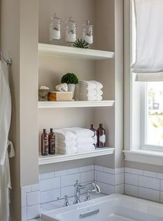 White stacked floating shelves are mounted in a nook above a drop in bathtub fitted with a white subway tiled deck holding a polished nickel vintage hook and spout tub filler in front of white subway backsplash tiles fixed beneath a window dressed in a white roman shade accenting gray wall paint. Vintage Bathrooms, Modern Bathroom, Bathroom Beach, Bathroom Shelf Decor, Bathroom Ideas, Bathtub Ideas, Bathroom Makeovers, Bathroom Niche, Bathrooms Decor