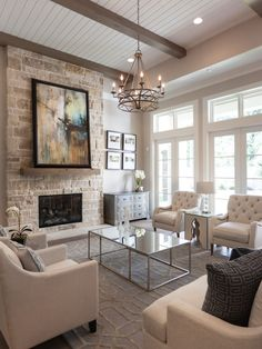 Living room with bead board ceiling, natural stone fireplace, french doors, wood beams, chandelier, abstract art | Frankel Building Group