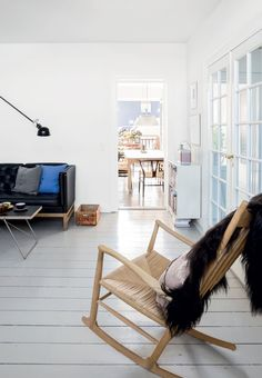 Bright living room with a wooden rocking chair designed by Hans J. Wegner.
