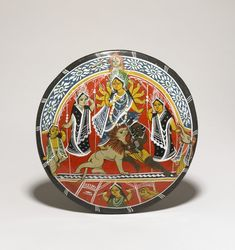 Sara (painted clay disc) depicting the goddess Durga, riding upon her vehicle, the lion. The pair are shown vanquishing the demon Mahi?asura. Durga is flanked on either side by her children: on her left, Karttikeya and Sarasvati and on her right, Lak?mi and Ga?esa. The plate has a red background and black border. The figures are delineated in white.