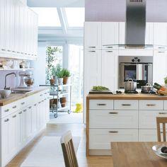 white shaker doors with wrap around butcher block countertop