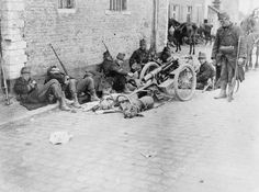 ANIMALS DURING FIRST WORLD WAR (Q 53207) Exhausted men and dogs of a Belgian machine gun section rest by the roadside in Louvain, during the restreat to Antwerp, 20 August 1914.
