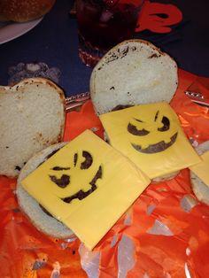 Hamburguesas con queso amarillo cortado en forma de calabaza.