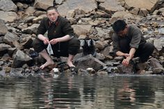 BY THE RIVER: North Korean soldiers washed their socks and hands on the banks of Yalu River, near Sinuiju, North Korea, opposite Liaoning province, China, Monday. (Jacky Chen/Reuters)