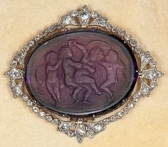 A very rare diamond and carved amethyst cameo brooch set in platinum with dancing nymphs and angels, circa 1910.