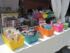 I'm liking the use of brightly coloured sets of baskets to organise and display (for example) different types of cards for sale on a stall.: