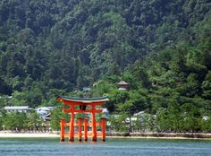 The Torii of Itsukushima Shrine [in Setonaikai National Park, the first of Japan's National Parks (established 1934)] rises above the waters of the Inland Sea against the forested background of the town of Miyajima, Hiroshima Prefecture, Japan.