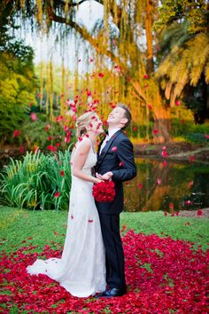 newlyweds under falling red rose petals! // photo by RenscheMari.com