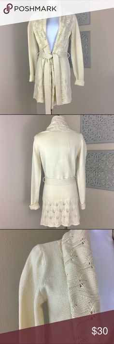Ezra Women's Cream Crochet Sweater Robe This Cream Crochet Robe Sweater by Ezra can be tied in the front or worn open. Super comfortable and cute! There is a dark mark on the lower sleeve (near the wrist) and has a few minor snags in the sleeves. 100% Acrylic. Hand wash & line dry Ezra Sweaters