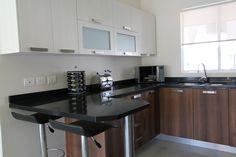Blanco y negro siempre será una combinación elegante. La madera le da un toque clásico. Una barra desayunadora para practicidad. Tips de decoración para tu casa.