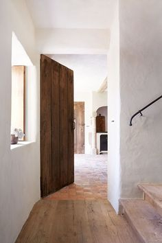 Elegant white hallway with wood in Hallway Design Ideas. A white minimal hallway with wooden floors and stair. Family home in restored and modernised barn: pale and rustic country interiors. Exterior Design, Interior And Exterior, White Hallway, Flur Design, Hallway Designs, Hallway Ideas, Menorca, Internal Doors, Rustic Design