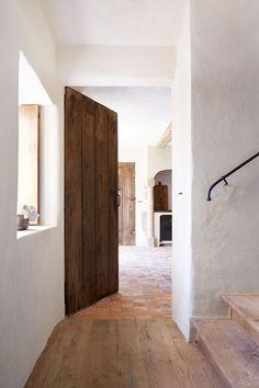 Elegant white hallway with wood in Hallway Design Ideas. A white minimal hallway…